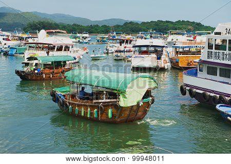 Man rides fishing boat at Sing Kee harbor in Hong Kong, China.