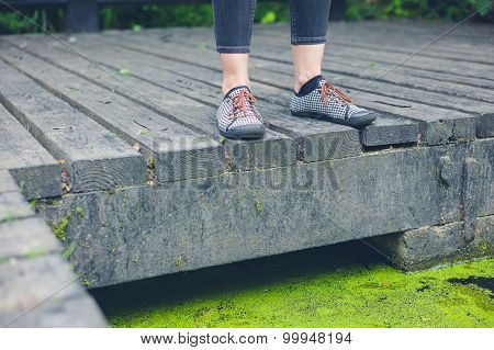 Feet Of Woman Standing On Deck By Pond