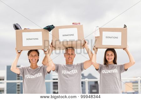 Portrait happy volunteers carrying donation boxes on their head on roof of building