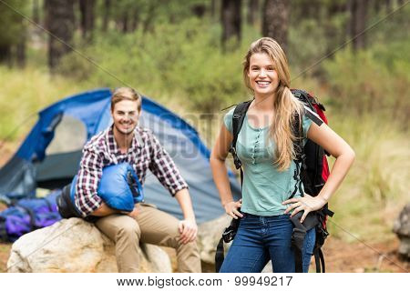 Portrait of a young pretty hiker couple holding a sleeping bag and backpack in the nature