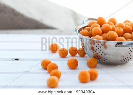 Yellow Plums In A Colander On A White Board