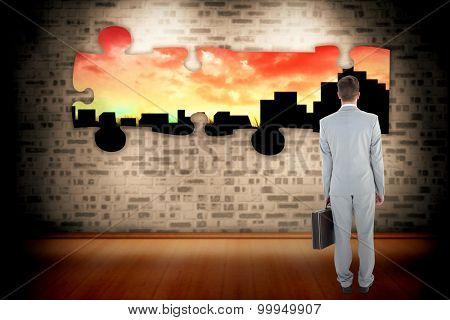 Businessman holding his briefcase against cityscape stencil on red sky