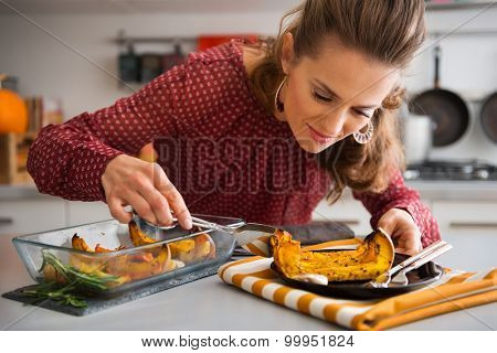 Elegant Woman Leaning Over Dish As She Is Serving Pumpkin