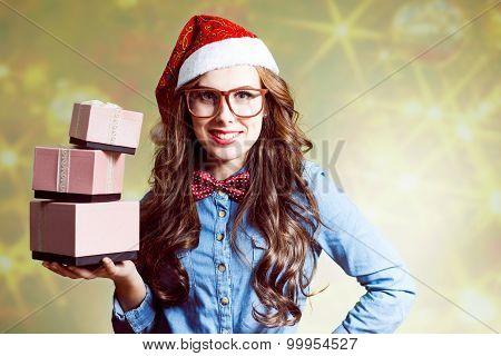 Content young female in Christmas hat holding  three present boxes