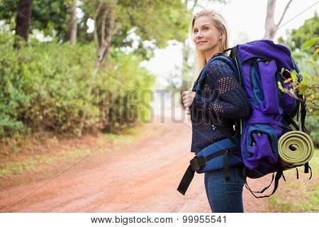 Side view of a female hiker waiting by the side of the road