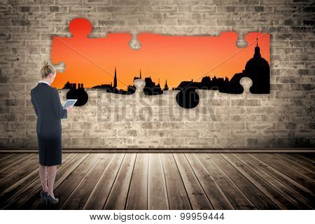 Businesswoman holding new tablet against cityscape stencil on red sky