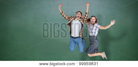 Geeky hipsters jumping and smiling against green chalkboard