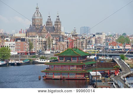 View to the city of Amsterdam with historic buildings and basilica of Saint Nicholas in Amsterdam.