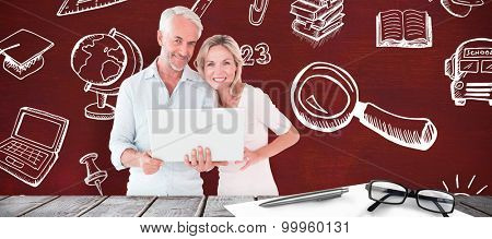 Mature students using laptop against desk