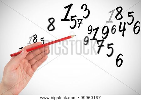 Hand holding red pencil against numbers