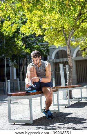 Handsome athlete tying shoelaces on a bench on a sunny day