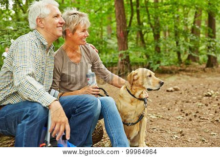 Relaxed senior couple sitting with dog in a forest during a hiking trip