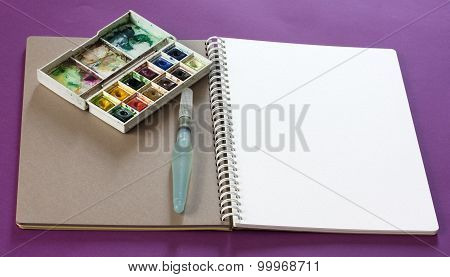 An open sketchbook with a blank white page, with a water brush and a box of watercolours