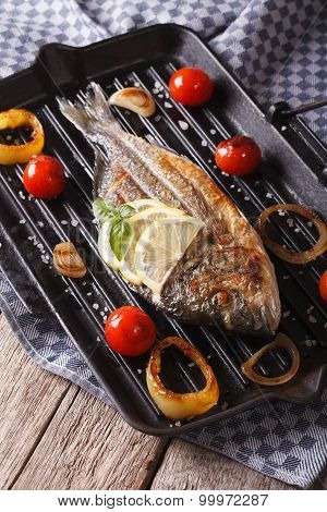 Dorado Fish With Vegetables Close Up On A Grill Pan On The Table. Vertical