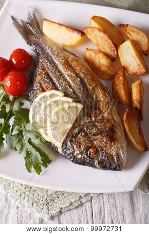 Grilled Dorado Fish With Fried Potatoes And Lemon Closeup. Vertical