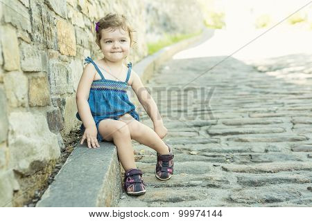 Little girl in an urban setting smiles at the camera.