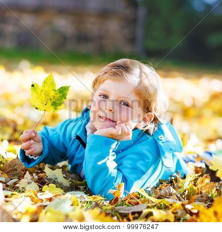 Little Kid Boy With Yellow Autumn Leaves In Park