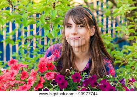 Young woman holding flower plants.