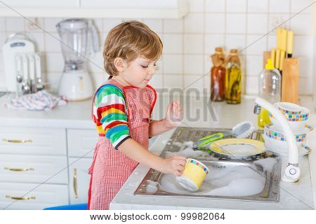 Funny Blond Kid Boy Washing Dishes In Domestic Kitchen