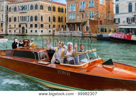 People in fancy dress ride on Grand Canal, Venice