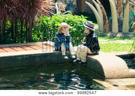 Ceramic Woman And Man On The Edge Of A Fish Pool For Garden Decorate.