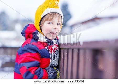 Little Kid Boy Eating And Tasting Snow, Outdoors On Cold Day