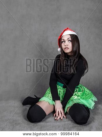 Young Attractive Woman In A Bright Green Skirt And Christmas Hat