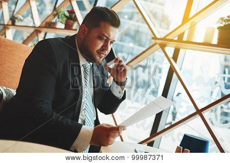 Portrait Of Successful Business Man Talking On Smart Phone Inside Coffee Shop. Attractive Adult Man