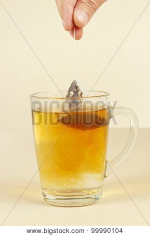 Hand brews tea bag in glass of hot water