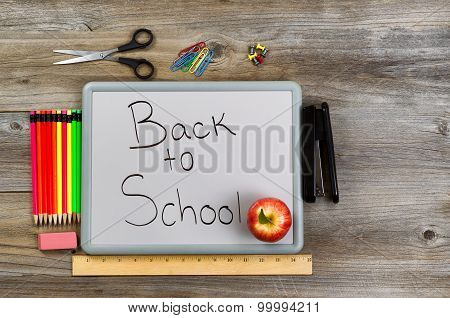 Back To School On White Board With School Supplies