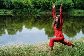 stock photo of virabhadrasana  - Beautiful young woman performing yoga exercises on the lake - JPG