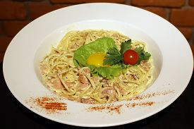 picture of carbonara  - Appetizing classical pasta carbonara with bacon egg yolk parmesan cheese decorated with leaf lettuce and red cherry tomato on white round plate closeup horizontal picture - JPG